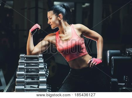 Slim Bodybuilder Girl Shows Biceps While Training In The Gym. Sports Concept Fat Burning And A Healt