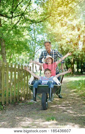 Daddy riding kids in wheelbarrow
