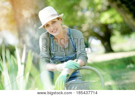 Blond woman with hat gardening on sunny day