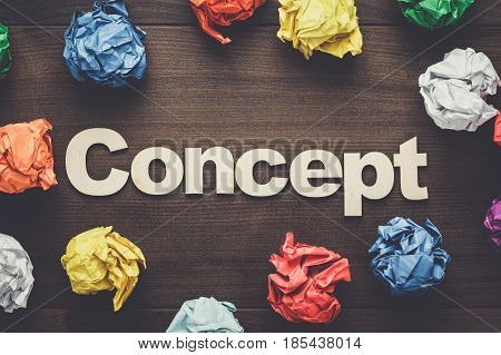 word concept and crumpled colorful paper. word concept on wooden background. brainstorm concept. wooden letters forming word concept