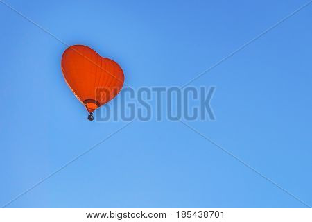Hot air balloon with a red dome in the shape of heart on blue sky background. Aerostat high in the sky with copy space.