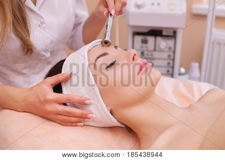 The Doctor-cosmetologist Makes The Procedure Microdermabrasion Of The Facial Skin Of A Beautiful, Yo