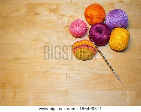 knitting in progress and colorful cotton thread balls on the wooden background with space