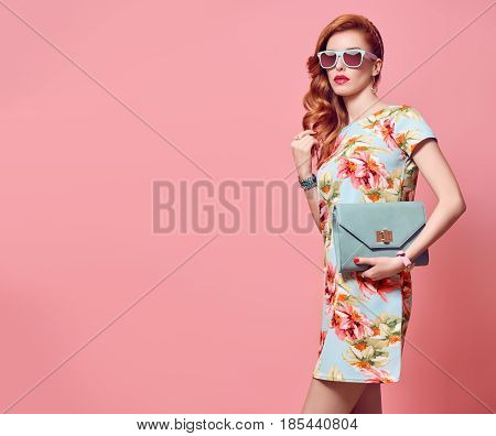Fashion Beauty woman in Trendy Summer Dress. Stylish wavy hairstyle, fashion Sunglasses, Summer Floral Outfit Luxury Clutch. Glamour Sexy Redhead Model in fashion pose. Playful summer Girl on Pink