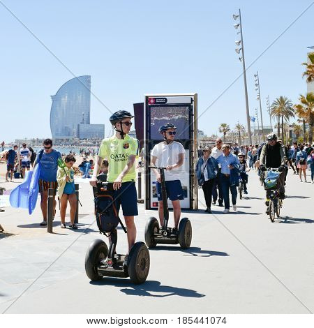 BARCELONA, SPAIN - MAY 7, 2017: Some people walking and some other people taking a segway tour by the seafront of the Barceloneta Beach in Barcelona, Spain, with the W Hotel in the background