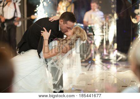 Groom Bends Bride Over Dancing In White Restaurant Hall Full Of Bengal Fires