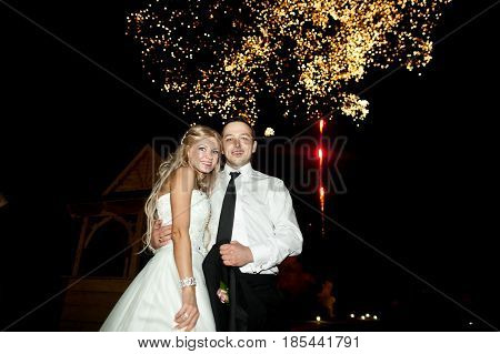 Happy Wedding Couple Stands Under The Night Sky Blowen With Fireworks