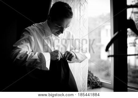 Man in white shirt stands at the window holding jacket in his hands