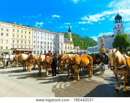 Central place in Salzburg city , Austria with carriages and horses