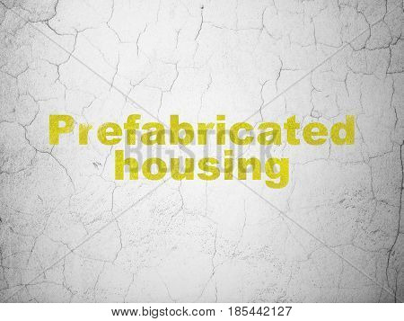 Construction concept: Yellow Prefabricated Housing on textured concrete wall background