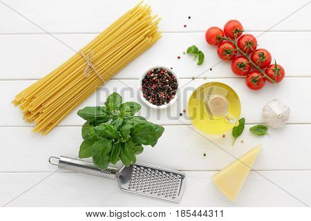 Bucatini with tomatoes basil oil cheese and spices on white wooden background. Italian pasta with other ingredients for cooking mediterranean dish. Top view concept healthy food.