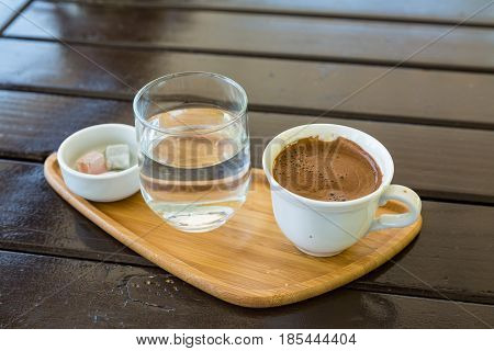 Turkish coffee on the wood with glass of water and turkish delights