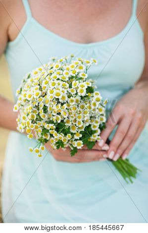beautiful girl in a summer blue dress holds a bouquet of fresh field camomiles in hand. Tenderness, love, wedding, summer mood - concept.