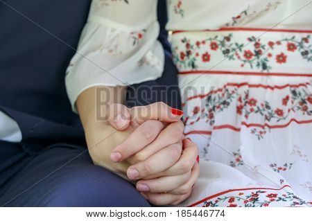 Couple holding hands while sitting together close