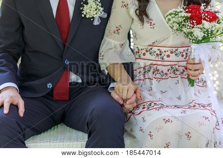Couple holding hands while sitting together with flowers