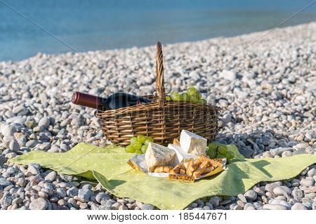 Picnic basket with wine, cheese and grapes on a sea beach