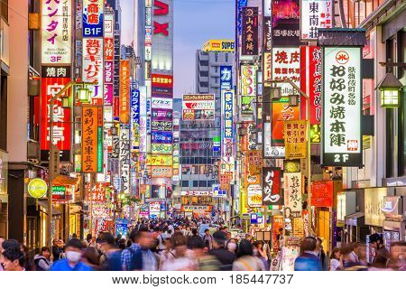 TOKYO, JAPAN - MAY 7, 2017: Crowds pass through Kabukicho in the Shinjuku district. The area is an entertainment and red-light district.