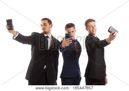 Three guys in suits making goofy selfies