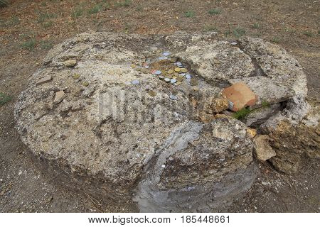 Ancient stone altar with a coins on it
