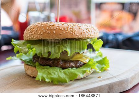 Delicious fresh hamburger cheeseburger with grilled beef burger, cheese on a table in restaurant