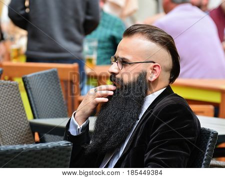 CLUJ-NAPOCA, ROMANIA - MAY 7, 2017:  Elegant middle aged business man sits at a street cafe table with a modern slicked back disconnected undercut hairstyle with shaved sides and a long black beard.