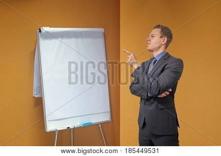 Young businessman with sceptical, critical or analyzing expression. Presentation in the office.