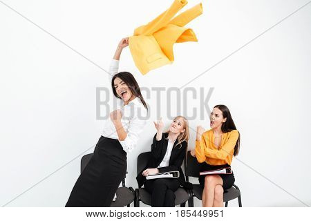 Image of angry women looking at happy lady colleague looking at camera make winner gesture.