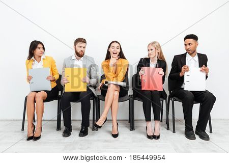 Photo of a happy woman looking at camera while her confused colleagues sitting in office looking at her.