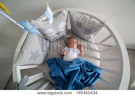 newborn lies in the round white bed with mobile and toys