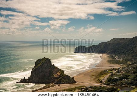 Auckland New Zealand - March 2 2017: Aerial view on the Lion rock at sandy Piha Beach under blue sky with white clouds. Tasman Sea surf forests cliffs and village.