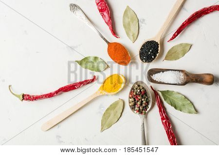 Spices In Different Spoons On A Stone White Background.