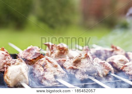 Grilled kebab cooking on metal skewer closeup. Roasted meat cooked at barbecue. Traditional eastern dish shish kebab. Grill on charcoal and flame.