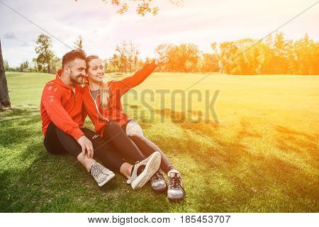 Sport man and woman making selfies in green park or forest while sitting on green grass. Happy couple hugging and posing for camera. Toned.