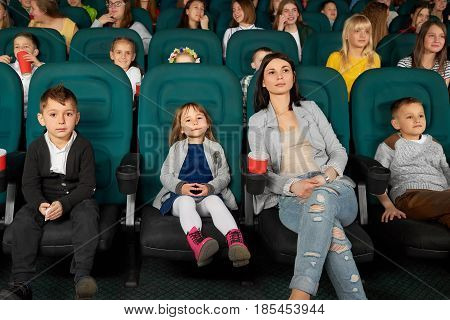 Full length shot of a beautiful young woman smiling watching a movie with her kids at the local cinema entertainment family parenting motherhood kids mother parent leisure activity happiness concept.
