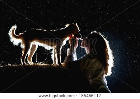 A silhouette of a young woman and her dog at night in the background of the starry sky. The hostess kisses her dog