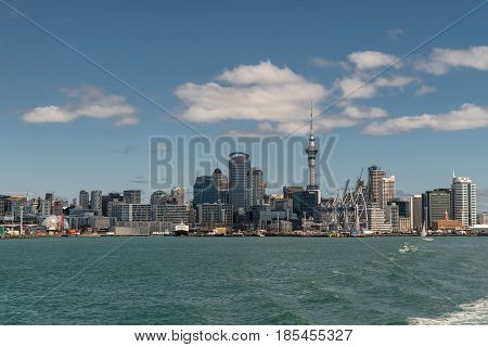 Auckland New Zealand - March 3 2017: Wide shot of the city skyline seen from greenish ocean water under blue sky with some white clouds. Highrises boats and specific buildings.
