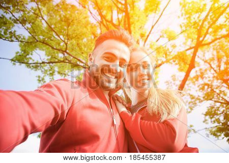 Nice portrait of sport man and woman making selfies in park after or before hard-working training day. Fitness, sports and lifestyle concepts. Toned.