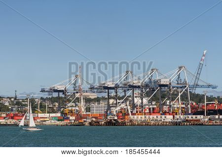 Auckland New Zealand - March 3 2017: The container terminal with its cranes and boxes under blue sky and behind greenish ocean water. White sailing boat in front. War Memorial Museum in back.