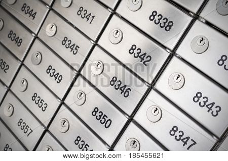Safety deposit box wallpaper. Numerous secure safety deposit boxes with lock and number plate. Silver metal. Insurance banking concept.