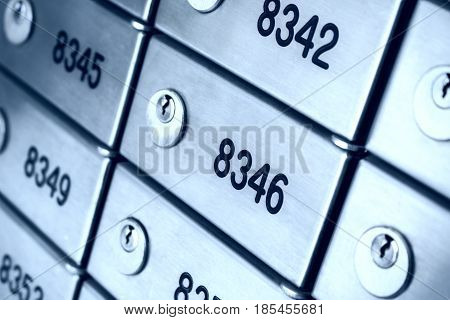 Safety deposit box wallpaper. Numerous secure safety deposit boxes with lock and number plate. Blue metal. Insurance banking concept.