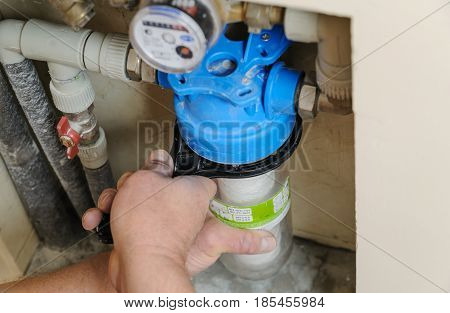 Man's hands fixing flask with a filter for water purification and protection of household appliances.
