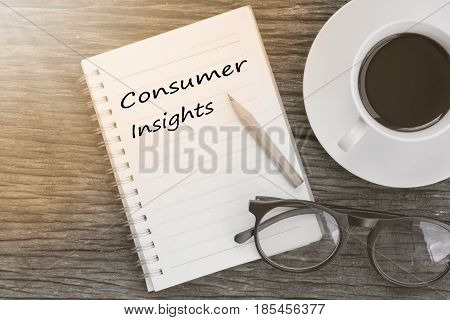 Concept Consumer insights message on notebook with glasses pencil and coffee cup on wooden table.