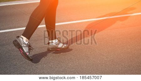 Jogging woman on track. Legs of woman running on road near park or forest. Closeup of female in running shoes going for run on road at sunrise or sunset. Toned.