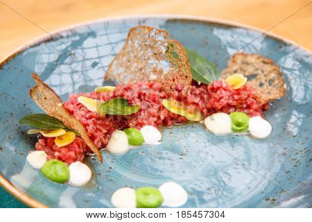 Beef Tartare With Slices Of Bread And Basil