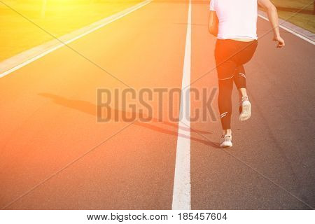 Jogging man along road. Closeup of male in running shoes going for run on road at sunrise or sunset. Fitness or sport concept. Toned.