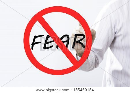 Businessman hand writing Fear prohibition sign concept with red marker on transparent wipe board.