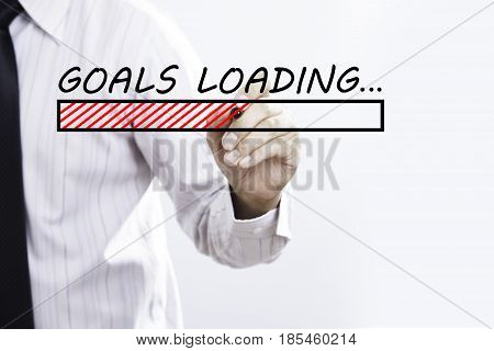 Businessman hand writing goals Loading with red marker on transparent wipe board business concept.