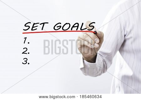 Businessman hand writing set goals with red marker on transparent wipe board business concept