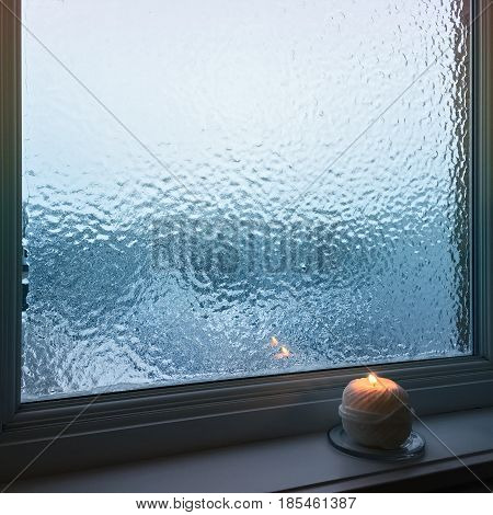 Blue frosted window and cozy candlelight. Winter composition.