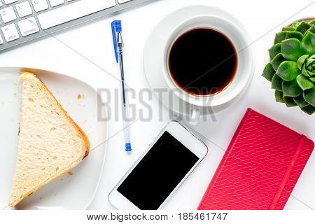 coffee break with sandwich, mobile phone, keyboard on woman office desk background top view